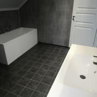 Ferdig baderom med flislagt gulv, Berry Alloc våtromsplater på vegg, badekar, ny innerdør, vask og speil.